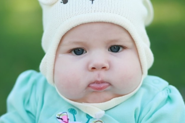 The way that this baby feels about having to wear this hat is the way that I feel about finding out I'm not allowed to complement people's fat babies anymore.